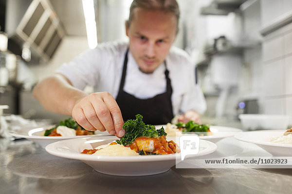 Chef garnishing food served in plate at restaurant