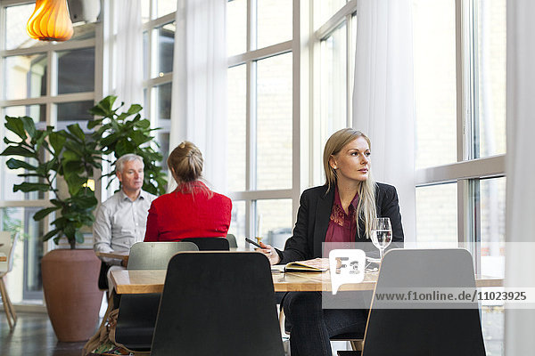 Thought businesswomen looking away while sitting at table in restaurant