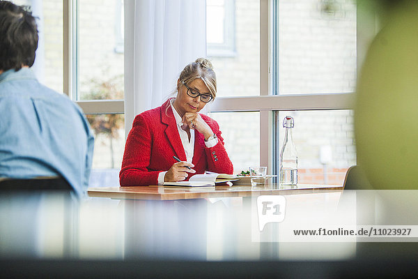 Concentrated businesswoman writing in book while sitting at table in restaurant