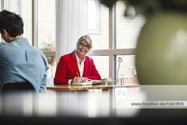 Happy businesswoman looking at colleague while sitting in restaurant