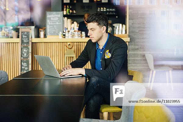 Businessman using laptop while sitting at restaurant