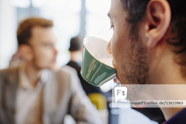 Cropped image of young man drinking tea at restaurant