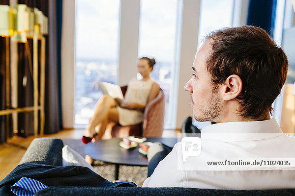 Businessman sitting on sofa while woman using laptop in background