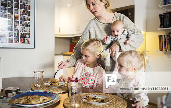Mother applying jam for daughters on pancakes at home