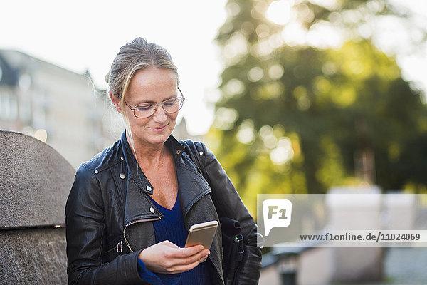 Mature woman looking at smart phone and smiling at street