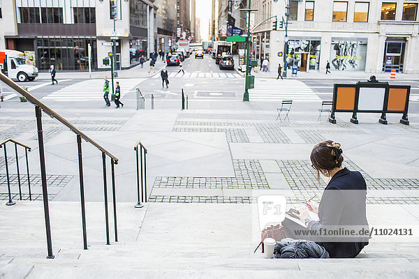 Rear view of businesswoman sitting on steps and working by city street