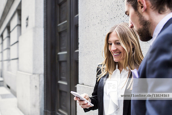 Smiling businesswoman showing smart phone to man while standing against building