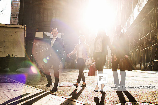Business people walking on street against buildings during sunny day