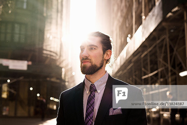 Close-up of young businessman standing against buildings on sunny day