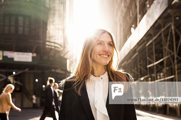 Smiling businesswoman standing on city street during sunny day