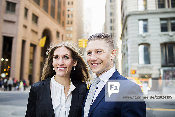 Smiling businessman and woman standing against buildings in city