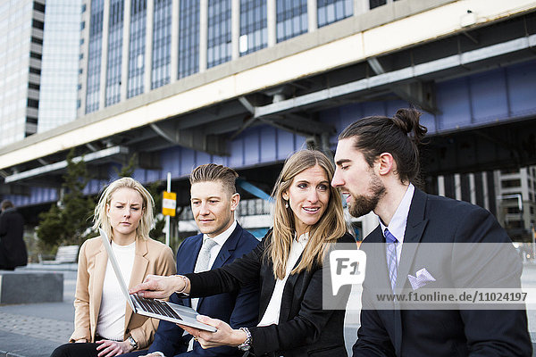 Businesswoman showing laptop to colleagues against buildings in city