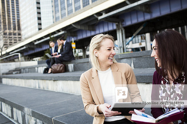 Happy colleagues with digital tablet with business people discussing in background