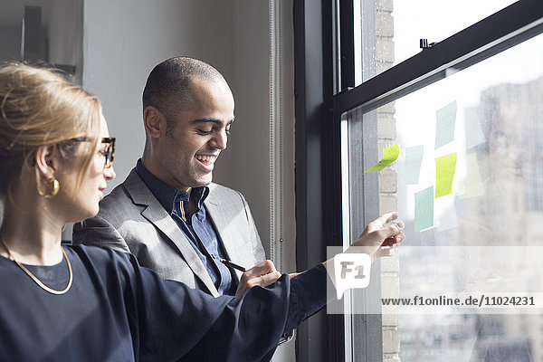 Businesswoman explaining about sticky notes to colleague at office