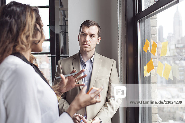 Businesswoman explaining to male colleague with sticky notes by window