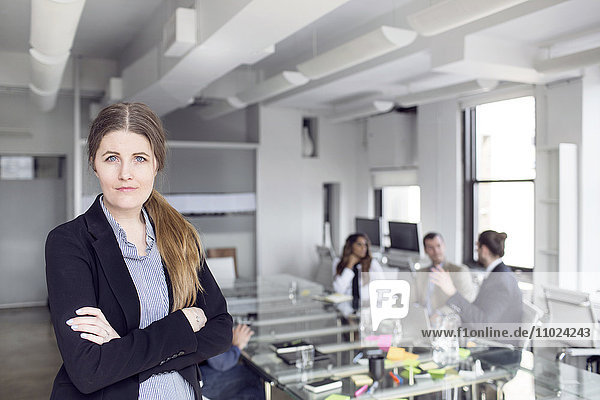 Portrait of confident businesswoman standing with colleagues discussing in background