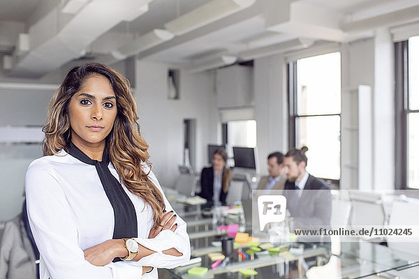 Confident businesswoman standing with arms crossed against colleagues at board room