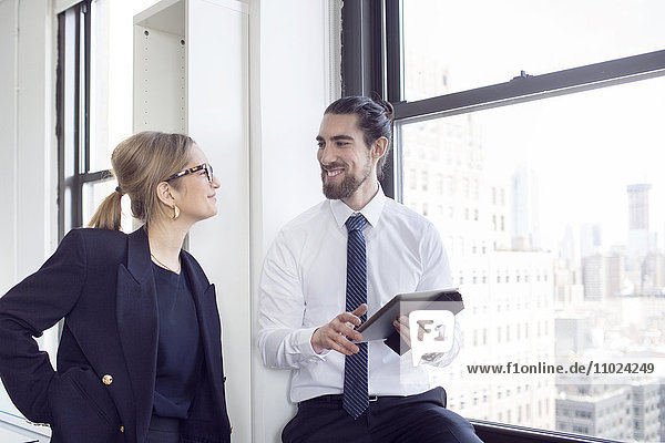 Smiling businessman talking to female colleague while holding digital tablet