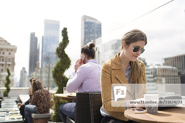 Businesswoman using digital tablet while people working in background