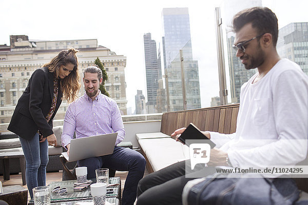 Businessman reading book while colleagues using laptop at rooftop restaurant