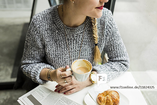 Midsection of smiling woman holding coffee cup while sitting at shop Midsection of smiling woman holding coffee cup while sitting at shop