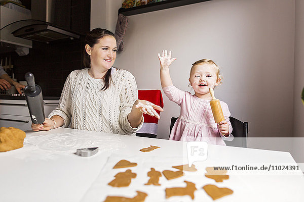 Happy mother and daughter enjoying while making cookies at table