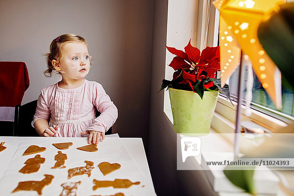 Girl looking through window while sitting with gingerbread cookies at home