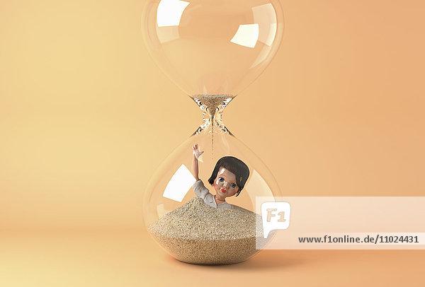 Puppe einer Geschäftsfrau versinkt im Sand einer Sanduhr