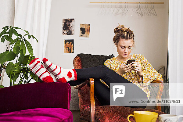 Woman using phone while resting on chair at home Woman using phone while resting on chair at home