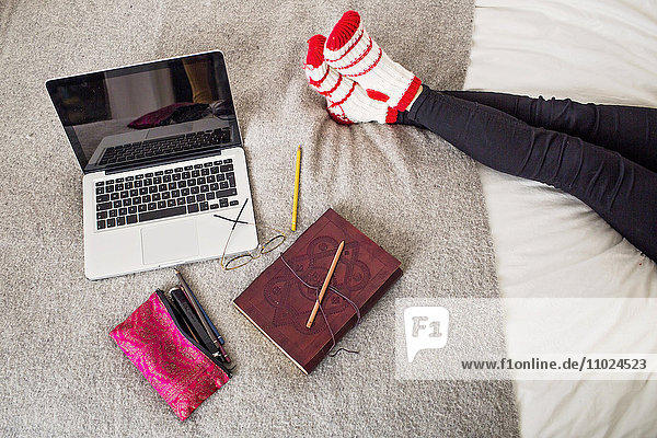 Low section of woman resting by laptop and book on bed at home Low section of woman resting by laptop and book on bed at home