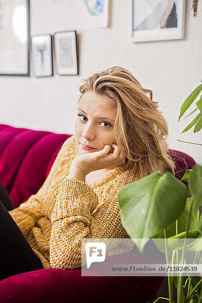 Portrait of beautiful woman sitting on sofa at home
