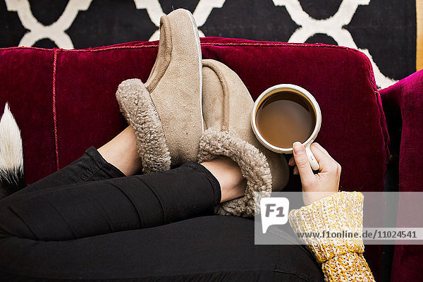 Low section of woman holding coffee cup while sitting on sofa at home Low section of woman holding coffee cup while sitting on sofa at home