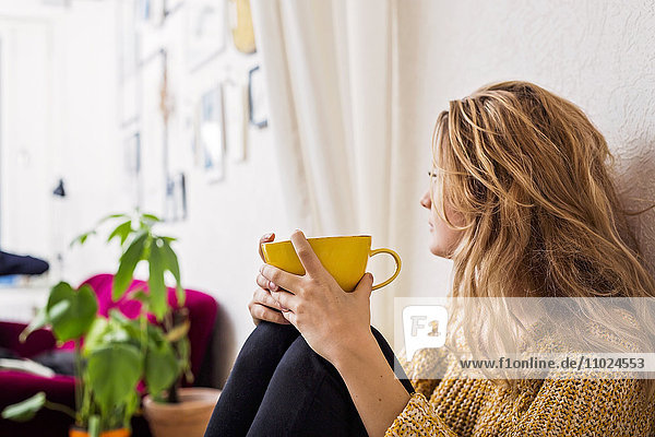 Woman holding coffee cup while sitting against wall Woman holding coffee cup while sitting against wall