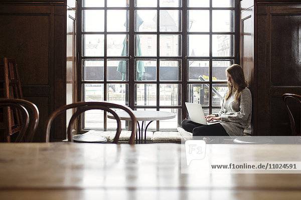 Woman using laptop while sitting by window at cafe