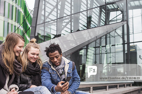 Friends looking at smart phone while sitting against glass building