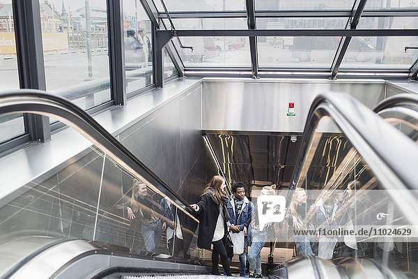 High angle view of friends moving up on escalator in glass building