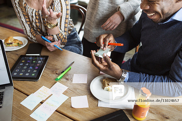 Friends using sticky notes while having sandwich at table in cafe