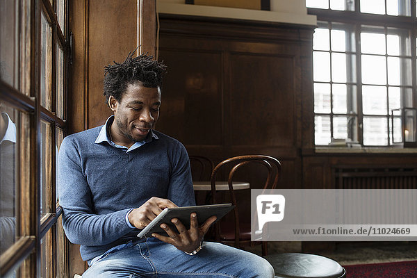 Young man using tablet while sitting at cafe