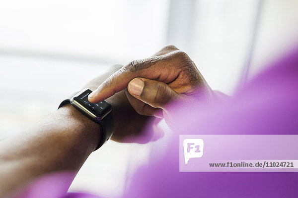 Cropped image of businessman using smart watch in office