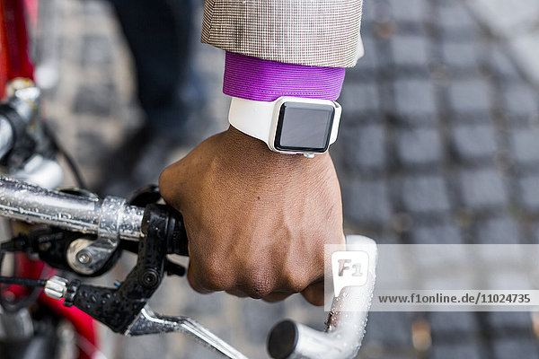 Cropped image of businessman wearing smart watch while riding bicycle on street