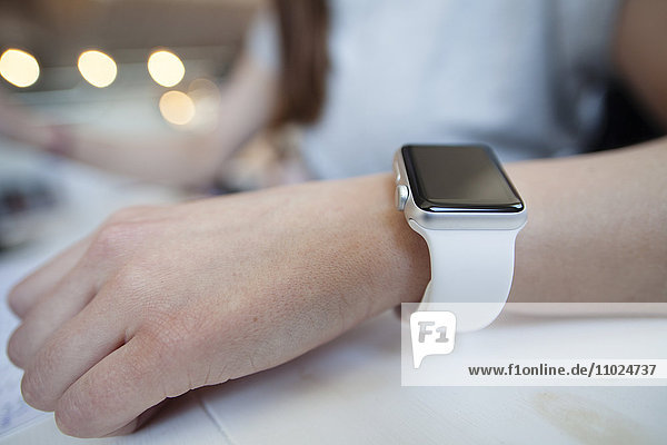 Close-up of woman wearing smart watch while sitting at desk in office