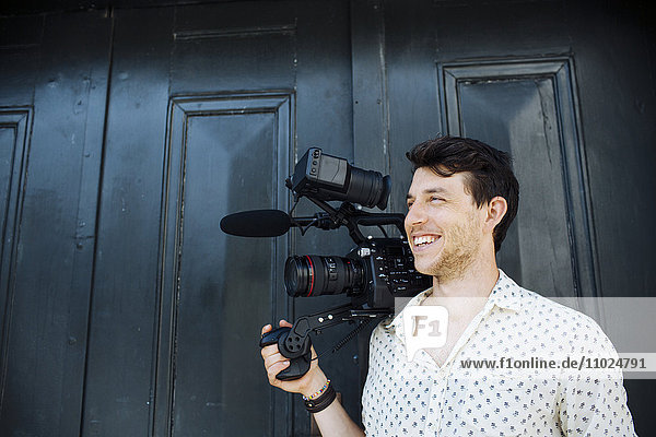 Happy man carrying digital video camera while standing against door