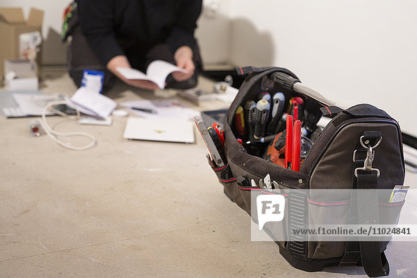 Close-up of tool bag while repairman working in background