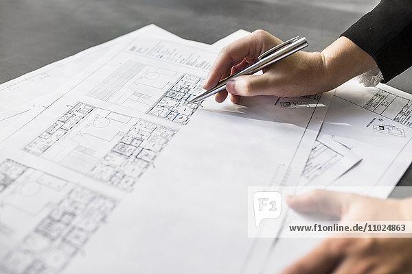 Cropped image of female architect working on blueprint