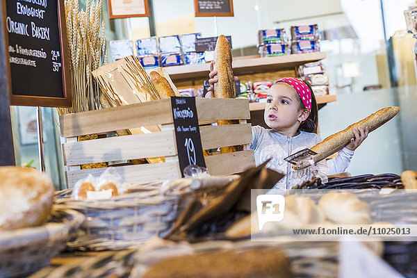 Cute girl buying breads in supermarket