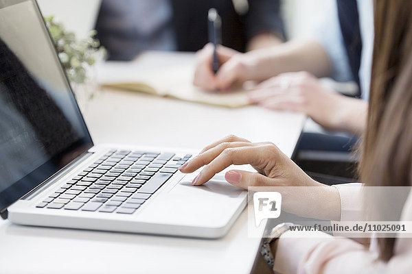 Cropped image of businesswoman using laptop at table in meeting
