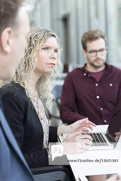 Businesswoman using laptop while sitting with colleagues at office