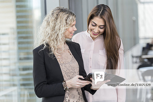 Happy businesswomen using digital tablet while standing in office