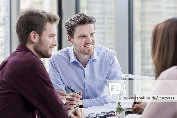Smiling businessmen looking at female colleague in meeting