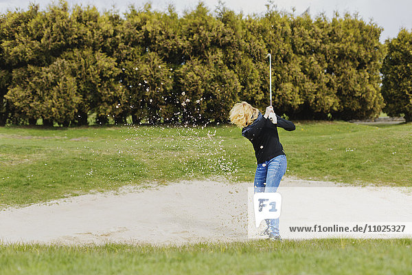 Woman playing golf on field against trees